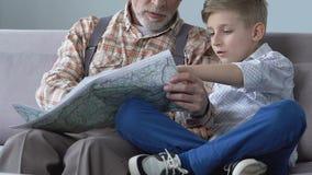 Συνταξιούχο άτομο που παρουσιάζει θέσεις ταξιδιού του στον εγγονό στο χάρτη, που προγραμματίζει το ταξίδι από κοινού απόθεμα βίντεο