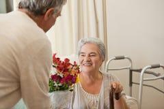 Συνταξιούχο άτομο που προσφέρει τα λουλούδια στη σύζυγό του Στοκ Εικόνες
