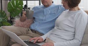 Συνταξιούχο ζεύγος με ένα φλιτζάνι του καφέ και lap-top στον καναπέ φιλμ μικρού μήκους