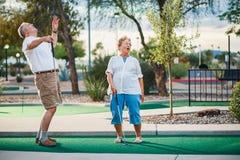 Συνταξιούχο ζεύγος που έχει τη διασκέδαση που παίζει το μίνι γκολφ στοκ εικόνες