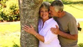 Συνταξιούχο ζεύγος που κλίνει ενάντια στο δέντρο που χαμογελά στη κάμερα απόθεμα βίντεο