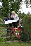 Συνταξιούχο ζεύγος σε έναν γύρο κύκλων που διαβάζει το χάρτη τους Στοκ φωτογραφία με δικαίωμα ελεύθερης χρήσης