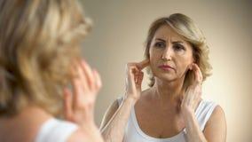 Συνταξιούχο θηλυκό σχετικά με το πρόσωπό της και σκέψη για τη πλαστική χειρουργική, αντανάκλαση απόθεμα βίντεο