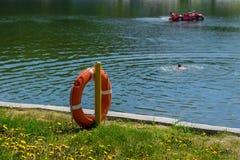 Συντηρητικό ζωής στην ακτή της λίμνης στους κολυμπώντας ανθρώπους υποβάθρου Στοκ Φωτογραφία