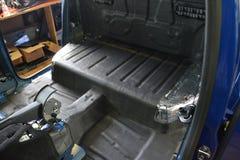 Συντονισμός του αυτοκινήτου σε ένα σώμα ανοιχτών φορτηγών με τρία στρώματα της μόνωσης θορύβου Στοκ Φωτογραφίες
