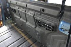 Συντονισμός του αυτοκινήτου σε ένα σώμα ανοιχτών φορτηγών με τρία στρώματα της μόνωσης θορύβου Στοκ Φωτογραφία