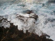 Συντρίβοντας κύματα στις ακιδωτές άκρες του μαύρου βράχου στοκ εικόνες