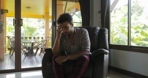 Συντριμμένη επικεφαλής συνεδρίαση λαβής ατόμων στην πολυθρόνα στο σπίτι, λυπημένος τύπος φυλών μιγμάτων που ματαιώνεται κατοχή τω απόθεμα βίντεο