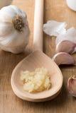 Συντριμμένο σκόρδο στο ξύλινο κουτάλι εκτός από τα Unpeeled γαρίφαλα Στοκ Εικόνες
