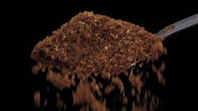 Συντριμμένο turmeric που πέφτει από το κουτάλι σιδήρου, μαύρο στούντιο υποβάθρου, σε αργή κίνηση φιλμ μικρού μήκους