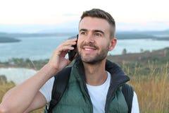 Συντροφικός τουρίστας που καλεί με τηλεφωνικό τηλέφωνο στα βουνά με μια πανέμορφη άποψη στοκ εικόνες