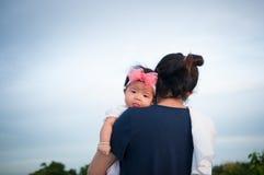 Συνδέοντας έννοια ημέρας μητέρων με τη νεογέννητη περιποίηση μωρών Η μητέρα κρατά το νεογέννητο μωρό με ρόδινο headband λουλουδιώ Στοκ φωτογραφία με δικαίωμα ελεύθερης χρήσης