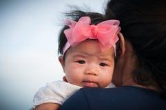 Συνδέοντας έννοια ημέρας μητέρων με τη νεογέννητη περιποίηση μωρών Η μητέρα κρατά το νεογέννητο μωρό με ρόδινο headband λουλουδιώ Στοκ Εικόνα