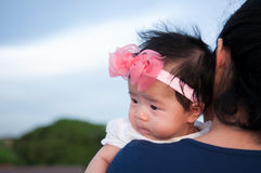 Συνδέοντας έννοια ημέρας μητέρων με τη νεογέννητη περιποίηση μωρών Η μητέρα κρατά το νεογέννητο μωρό με ρόδινο headband λουλουδιώ Στοκ Φωτογραφίες