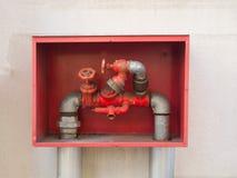 Συνδέσεις μανικών πυρκαγιάς οικοδόμησης ` s με τις κόκκινες λαβές σε ένα κόκκινο κιβώτιο Στοκ φωτογραφία με δικαίωμα ελεύθερης χρήσης