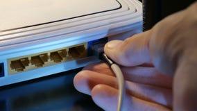 Συνδέστε το RJ45 καλώδιο με το δρομολογητή WiFi απόθεμα βίντεο