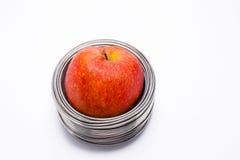 Συνδεμένο με καλώδιο μήλο: ολόκληρο κόκκινο μήλο στις σπείρες του καλωδίου αργιλίου που απομονώνεται Στοκ εικόνες με δικαίωμα ελεύθερης χρήσης