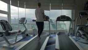 Συνδετήρας της γυναίκας treadmill στο κέντρο ικανότητας που εξετάζει το παράθυρο με τη εικονική παράσταση πόλης Χογκ Κογκ, Κίνα φιλμ μικρού μήκους