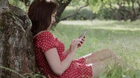Συν τη συνεδρίαση κοριτσιών μεγέθους στη χλόη κάτω από το δέντρο και τη χρησιμοποίηση του smartphone της φιλμ μικρού μήκους