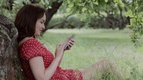 Συν τη συνεδρίαση κοριτσιών μεγέθους στη χλόη κάτω από το δέντρο και τη χρησιμοποίηση του smartphone της απόθεμα βίντεο