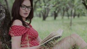 Συν το μέγεθος η συνεδρίαση κοριτσιών στη χλόη κάτω από το δέντρο και διαβάζει ένα βιβλίο απόθεμα βίντεο