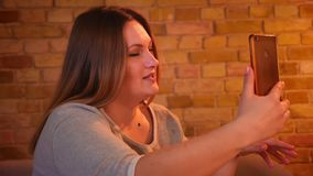 Συν το μέγεθος το θηλυκό πρότυπο που έχει ένα βίντεο καλεί το smartphone και καθορισμός της τρίχας της prettily στην άνετη εγχώρι απόθεμα βίντεο