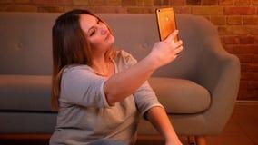 Συν το πρότυπο μεγέθους με τις μακρυμάλλεις όμορφες selfie-φωτογραφίες παραγωγής που δίνουν πέντε στο smartphone στην άνετη εγχώρ απόθεμα βίντεο