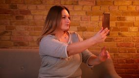 Συν το πρότυπο μεγέθους με τις μακρυμάλλεις όμορφες selfie-φωτογραφίες παραγωγής που χρησιμοποιούν το smartphone στην άνετη εγχώρ απόθεμα βίντεο