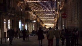 Συρακούσες, Ιταλία, Σικελία - Δεκέμβριος: Τα χαρακτηριστικά παλαιά πόλης Χριστούγεννα οδών ανάβουν τους περπατώντας ανθρώπους απόθεμα βίντεο