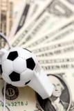 Συριγμός ποδοσφαίρου στις σημειώσεις δολαρίων Στοκ Φωτογραφία