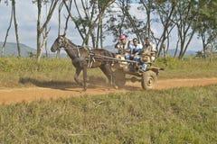 Συρμένο άλογο κάρρο και τρεις άνθρωποι που ταξιδεύουν μέσω της επαρχίας της κεντρικής Κούβας Στοκ εικόνες με δικαίωμα ελεύθερης χρήσης