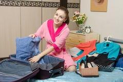 Συσκευάζει μια πετσέτα σε μια βαλίτσα Στοκ Εικόνες