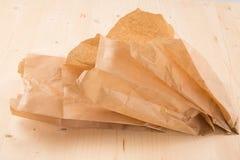 Συσκευάζοντας την ανακυκλωμένη σακούλα εγγράφου του Κραφτ στο ξύλινο υπόβαθρο με το ψαλίδισμα της πορείας στοκ φωτογραφίες