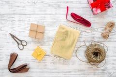 Συσκευάζοντας δώρο Κιβώτια δώρων, sciccors, λεπτό σκοινί, κορδέλλα στην γκρίζα ξύλινη τοπ άποψη υποβάθρου Στοκ Εικόνες