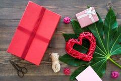 Συσκευάζοντας δώρο Κόκκινο κιβώτιο δώρων, sciccors, λεπτό σκοινί στη σκοτεινή ξύλινη τοπ άποψη υποβάθρου Στοκ Εικόνες