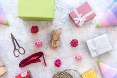 Συσκευάζοντας δώρο Χρωματισμένα κιβώτια δώρων, sciccors, λεπτό σκοινί, κορδέλλα, καπέλο κομμάτων στην γκρίζα τοπ άποψη υποβάθρου  Στοκ Εικόνα