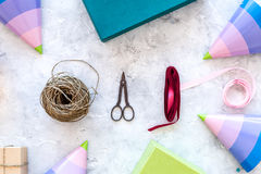Συσκευάζοντας δώρο Χρωματισμένα κιβώτια δώρων, sciccors, λεπτό σκοινί, κορδέλλα, καπέλο κομμάτων στην γκρίζα τοπ άποψη υποβάθρου  Στοκ Φωτογραφίες