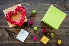 Συσκευάζοντας δώρο Χρωματισμένα κιβώτια δώρων, sciccors, λεπτό σκοινί στη σκοτεινή ξύλινη τοπ άποψη υποβάθρου Στοκ Φωτογραφία