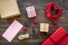 Συσκευάζοντας δώρο Χρωματισμένα κιβώτια δώρων, sciccors, λεπτό σκοινί στη σκοτεινή ξύλινη τοπ άποψη υποβάθρου Στοκ φωτογραφίες με δικαίωμα ελεύθερης χρήσης