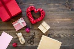 Συσκευάζοντας δώρο Χρωματισμένα κιβώτια δώρων, sciccors, λεπτό σκοινί στη σκοτεινή ξύλινη τοπ άποψη υποβάθρου copyspace Στοκ Φωτογραφία