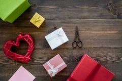 Συσκευάζοντας δώρο Χρωματισμένα κιβώτια δώρων, sciccors, λεπτό σκοινί στη σκοτεινή ξύλινη τοπ άποψη υποβάθρου copyspace Στοκ Εικόνα