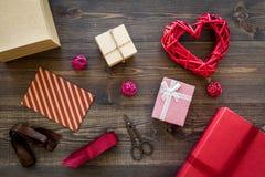 Συσκευάζοντας δώρο Χρωματισμένα κιβώτια δώρων, sciccors, κορδέλλα, λεπτό σκοινί στη σκοτεινή ξύλινη τοπ άποψη υποβάθρου Στοκ Φωτογραφίες
