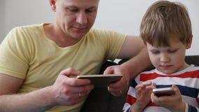 Συσκευές στη ζωή μιας σύγχρονης οικογένειας μπαμπάς με παίζοντας παιχνίδια τα μικρά γιων στα smartphones, που κάθονται στον καναπ απόθεμα βίντεο