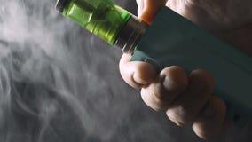 Συσκευή Vape - RDA και mech νεαρός δικυκλιστής στο αρσενικό χέρι με τα σύννεφα ή τον ατμό ατμού μεγάλου ποσού φιλμ μικρού μήκους