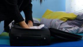 συσκευασία γυναικών επάνω τα ενδύματά της στη βαλίτσα και την αναχώρηση του σπιτιούη απόθεμα βίντεο