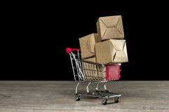 Συσκευασίες δεμάτων χαρτοκιβωτίων στο καροτσάκι αγορών Στοκ Φωτογραφία