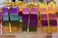 Συσκευασίες των ζωηρόχρωμων φραγμών σαπουνιών, χρυσή κορδέλλα στοκ φωτογραφίες