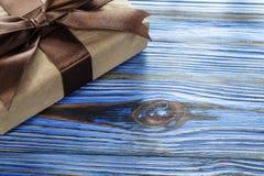 Συσκευασμένο καφετί παρόν κιβώτιο στον εκλεκτής ποιότητας ξύλινο πίνακα στοκ φωτογραφία