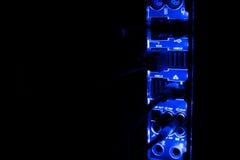Συσκότιση, θολωμένα σύνορα Κλείστε επάνω των μπλε καλωδίων δικτύων που συνδέονται με το μαύρο διακόπτη που καίγεται στο σκοτάδι Στοκ Εικόνες