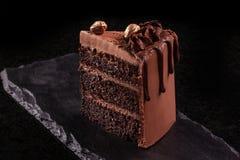 συσσωματώστε το κομμάτι σοκολάτας Mousse σοκολάτας φέτα κέικ σε έναν μαύρο πίνακα, μαύρο υπόβαθρο Στοκ Φωτογραφίες